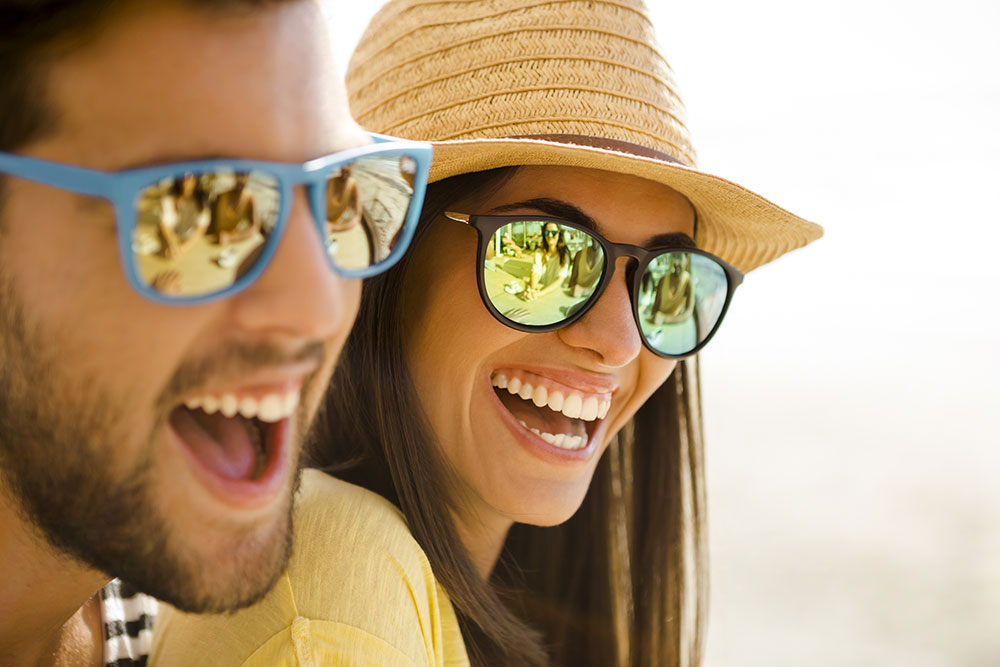 happy couple smiling wearing sunglasses